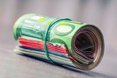 Euroanmerkungen mit Reflexion Fünf, 10 und fünfzig Eurobanknoten Fokus auf Seil Nahaufnahme von gerollte Eurobanknoten auf Beton  Stockbilder