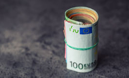 Euroanmerkungen mit Reflexion Fünf, 10 und fünfzig Eurobanknoten Fokus auf Seil Nahaufnahme von gerollte Eurobanknoten auf Beton  Lizenzfreies Stockfoto