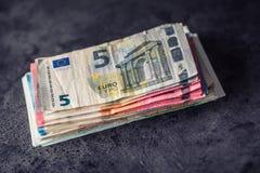 Euroanmerkungen mit Reflexion Fünf, 10 und fünfzig Eurobanknoten Fokus auf Seil Nahaufnahme von gerollte Eurobanknoten auf Beton  Stockfoto