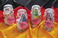 Euroanmärkningar i flaskor på tysk flagga Royaltyfri Foto