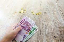500, 100 Eurobanknoten in der Hand vor dem hintergrund der Münzen lizenzfreies stockfoto