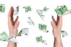Eurobanknoten, die auf junge männliche Hände fallen Lizenzfreie Stockfotos