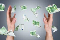 Eurobanknoten, die auf junge männliche Hände fallen Lizenzfreies Stockfoto