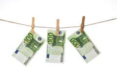 100 Eurobanknoten, die an der Wäscheleine auf weißem Hintergrund hängen Lizenzfreies Stockbild