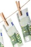 100 Eurobanknoten, die an der Wäscheleine auf weißem Hintergrund hängen Lizenzfreie Stockfotos