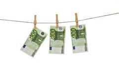 100 Eurobanknoten, die an der Wäscheleine auf weißem Hintergrund hängen Lizenzfreies Stockfoto