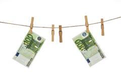 100 Eurobanknoten, die an der Wäscheleine auf weißem Hintergrund hängen Stockfotografie