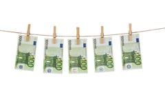 100 Eurobanknoten, die an der Wäscheleine auf weißem Hintergrund hängen Lizenzfreie Stockfotografie