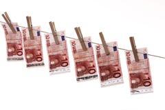 10 Eurobanknoten, die an der Wäscheleine hängen Stockfotos