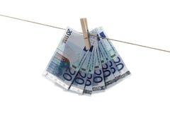 20 Eurobanknoten, die an der Wäscheleine hängen Stockbild