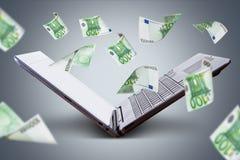 Eurobanknoten, die um Laptop fliegen Lizenzfreies Stockfoto