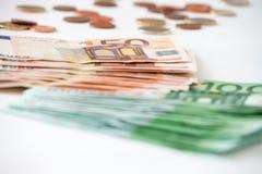 Eurobanknoten mit Euromünzen Stockfotografie