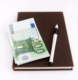 Eurobanknoten, Notizbuch und Stift Stockfotos