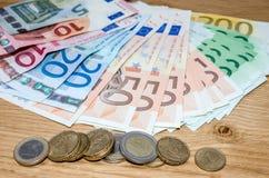 Eurobanknoten und Euromünzen Stockfotografie