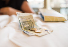 Eurobanknoten und Münzen liegen auf einer weißen Tischdeckenzahlung die Lieferung eines Frühstücksmittagessens Lizenzfreies Stockbild