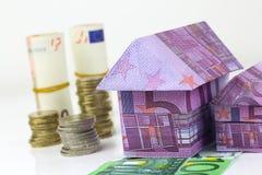 Eurobanknotenhaus und -münzen Stockfotografie