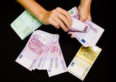 Eurobargeld in den Händen auf Schwarzem Lizenzfreie Stockfotos