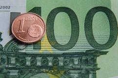 Eurocent och en sedel hundra euro Arkivbild