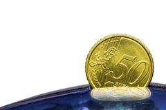Eurocent sätta femtio in i en blå sparbössa Royaltyfri Fotografi