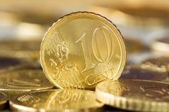 Eurocent tien die zich tussen andere muntstukken bevinden Stock Fotografie