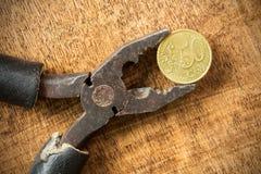 Eurocent und Zangen auf dem hölzernen Hintergrund Lizenzfreies Stockfoto