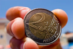 EuroCoin. FishEye closeup of a used 2 euro coin, held with a four finger grip Stock Photo