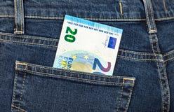Euroet för sedel som 20 klibbar ut ur den tillbaka jeansen, stoppa i fickan Arkivfoto