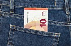 Euroet för sedel som 10 klibbar ut ur den tillbaka jeansen, stoppa i fickan Arkivfoto