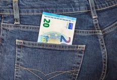 Euroet för sedel som 20 klibbar ut ur den tillbaka jeansen, stoppa i fickan Fotografering för Bildbyråer