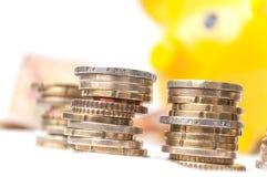 Euroet myntar högar och sedlar med gult piggy förbud Arkivfoto