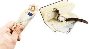 Euroet och anteckningsboken i hand med euro och klockan Royaltyfri Fotografi