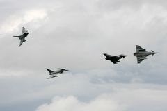 Eurofighters. Four RAF Typhoons split from formation at a flypast for the Queen at Fairford, UK royalty free stock photo