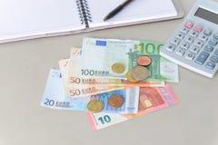 Eurogeldbanknoten und -münzen, die mit Taschenrechner, Notizbuch und Stift zählen Stockfoto