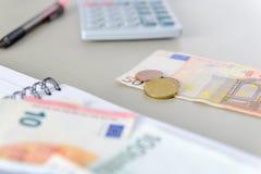 Eurogeldbanknoten und -münzen, die mit Taschenrechner, Notizbuch und Stift zählen Lizenzfreies Stockbild