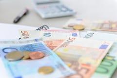 Eurogeldbanknoten und -münzen, die mit Taschenrechner, Notizbuch und Stift zählen Stockfotos