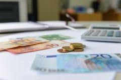 Eurogeldbanknoten und -münzen, die mit Taschenrechner, Notizbuch und Stift zählen Stockfotografie