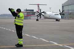 Eurolot taxiing. Polish company Eurolot taxiing on the apron with ramp agent marshalling Royalty Free Stock Photo