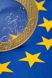 Euromünze auf europäischer Markierungsfahne lizenzfreies stockfoto