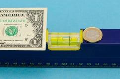 Euromünze der waagerecht ausgerichteten Hilfsmittel usd-Dollarbanknote auf Blau Lizenzfreies Stockbild