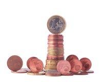 1 Euromünze, die auf Stapel Euromünzen umgeben durch stehende Münzen des kleineren Wertes steht Stockbilder