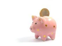1 Euromünze, die in Sparschwein fällt Lizenzfreie Stockbilder