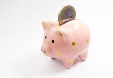 1 Euromünze, die in Sparschwein fällt Stockbilder