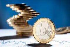 Euromünze mit einem Stapel Münzen im Hintergrund Lizenzfreies Stockfoto