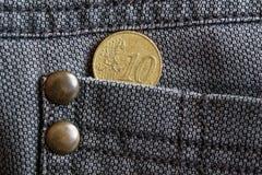 Euromünze mit einer Bezeichnung Eurocents 10 in der Tasche von abgenutzten braunen Denimjeans Lizenzfreies Stockbild