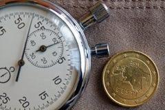 Euromünze mit einer Bezeichnung fifity von Eurocents (Rückseite) und von Stoppuhr auf altem beige Jeanshintergrund - Geschäftshin Lizenzfreie Stockbilder