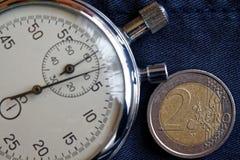 Euromünze mit einer Bezeichnung von 2 Euro und von Stoppuhr auf veraltetem blauem Denimhintergrund - Geschäftshintergrund Stockfoto