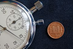 Euromünze mit einer Bezeichnung von 1 Eurocent (Rückseite) und von Stoppuhr auf abgenutztem schwarzem Denimhintergrund - Geschäft Lizenzfreie Stockfotos
