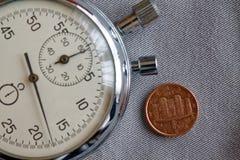 Euromünze mit einer Bezeichnung von 1 Eurocent (Rückseite) und von Stoppuhr auf grauem Denimhintergrund - Geschäftshintergrund Lizenzfreie Stockfotografie