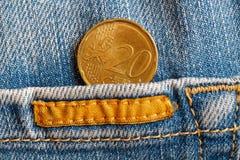 Euromünze mit einer Bezeichnung von 20 Eurocents in der Tasche von abgenutzten blauen Denimjeans mit gelbem Streifen Lizenzfreies Stockbild