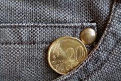 Euromünze mit einer Bezeichnung von 20 Eurocents in der Tasche von abgenutzten braunen Denimjeans Lizenzfreies Stockbild